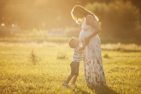 ילד מנשק את הבטן של אמא שלו שבהריון